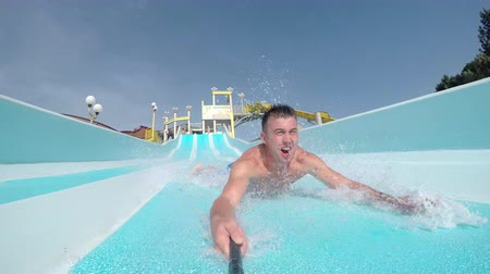 SELFIE: Cheerful smiling man sliding down super fast water slide in waterpark on a beautiful summer day