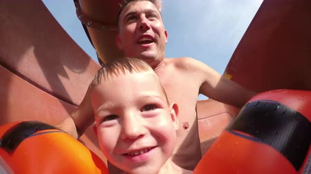 toboggan : SELFIE: Young father and son sliding down the water slide in sunny summer in fun aqua park