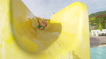 SLOW MOTION: Happy cheerful kid smiling sliding down the toboggan with hands raised in aquapark on a beautiful sunny day in summer 무비클립