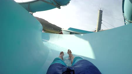 FPV FIRST PERSON VIEW POV: Young adult man sliding down the fun water slide at summer sunset in summer water park