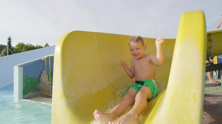 SLOW MOTION CLOSEUP: Happy boy sliding down the water slide toboggan smiling with hands raised up on a beautiful sunny day at summer sunset Wideo