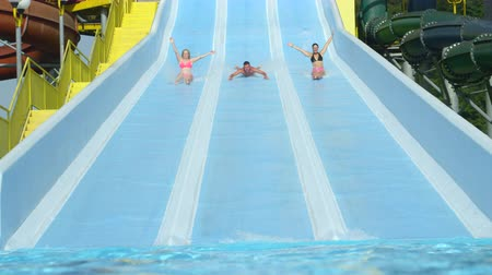kabarık : SLOW MOTION: Cheerful young adults sliding down extreme water slide toboggan screaming and smiling in hot summer on vacation Stok Video