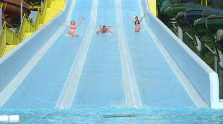 toboggan : SLOW MOTION CLOSEUP: Happy friends sliding down extreme water slide toboggan smiling and screaming on sunny holidays in hot summer