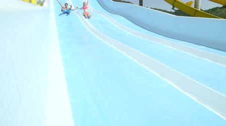 waterslide : SLOW MOTION CLOSE UP: Happy young couple on their date smiling and sliding down the extreme fast water slide toboggan in aqua park on a beautiful sunny day in hot summer