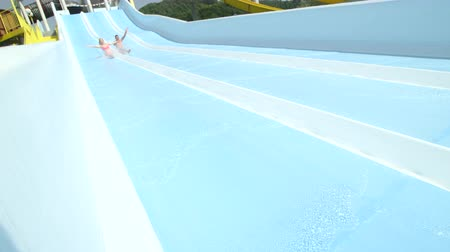 waterslide : SLOW MOTION: Cheerful happy couple holding hands and sliding down the extreme fast water slide toboggan smiling and waving into the camera on their romantic date in sunny summer