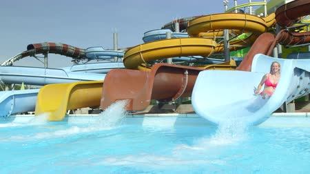 waterslide : SLOW MOTION: Cheerful woman sliding down the water slide falling into pool in fun aquapark on a hot summer day Stock Footage