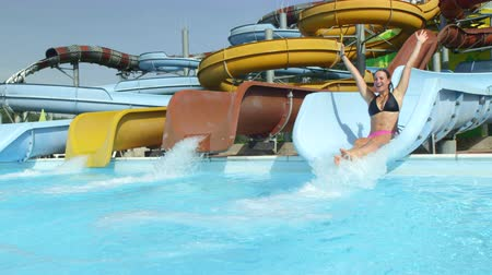 SLOW MOTION: Happy woman sliding down the toboggan splashing into water in water park in summer vacation