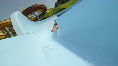toboggan : SLOW MOTION CLOSE UP: Happy woman sliding down the water slide smiling