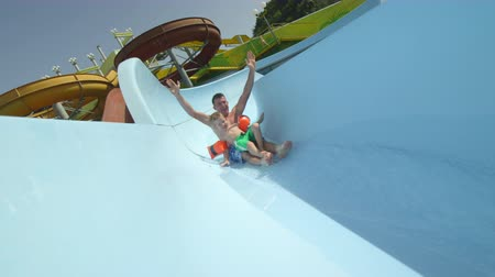 SLOW MOTION: Happy father and kid sliding down the water slide smiling with hands raised on a beautiful summer day on sunny vacations