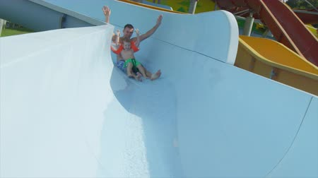SLOW MOTION: Happy father and son sliding the water slide toboggan in aqua park on sunny holidays