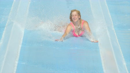 waterslide : SLOW MOTION: Excited young woman sliding on super fast extreme water slide toboggan, water spraying around