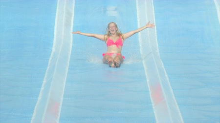 waterslide : SLOW MOTION: Happy woman sliding down the fast water slide toboggan in sunny summer in fun aqua park Stock Footage