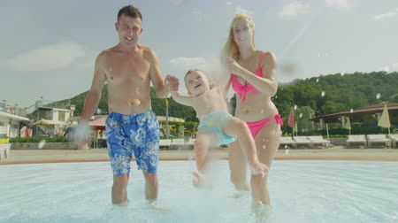 waterslide : SLOW MOTION: Playful young parents playing with happy infant baby boy, swinging their smiling kid back and forth, splashing pool water into the camera on sunny summer day in fun water park Stock Footage