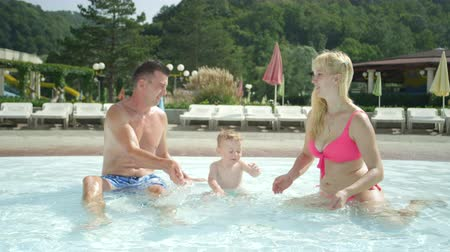 SLOW MOTION: Happy young family, happy blonde mother and father playing with their infant baby boy in shallow pool, splashing water drops in fun aqua park on their fun vacations in sunny summer