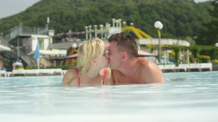 SLOW MOTION CLOSE UP PORTRAIT: Happy young couple laying in shallow pool and kissing on a beautiful summer day in fun aqua park