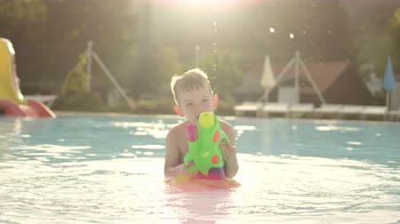 squirting : SLOW MOTION: Happy kid squirting water drops with water gun directly into camera at beautiful golden summer sunset in fun aqua park Stock Footage