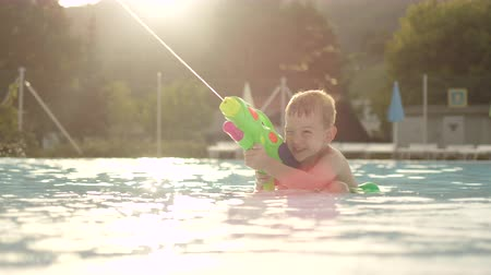 SLOW MOTION CLOSE UP: Young boy in shallow pool aiming and shooting with fun water gun in aqua park at beautiful golden sunset Wideo