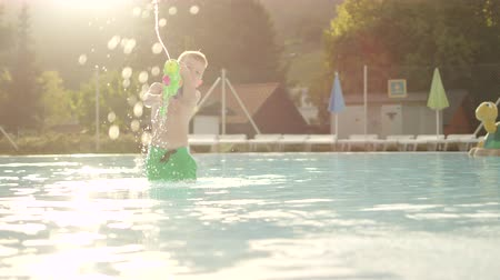 squirting : SLOW MOTION: Happy boy playing with water gun in pool on sunny vacations at beautiful summer sunset