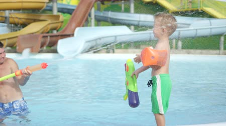 SLOW MOTION: Father and son having a water gun fight in a pool on a beautiful summer day in water park Wideo