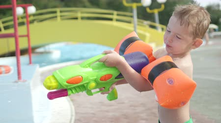 squirting : SLOW MOTION CLOSE UP: Young boy kid having a water fight, shooting his father and he gets splashed back in sunny summer in fun water park