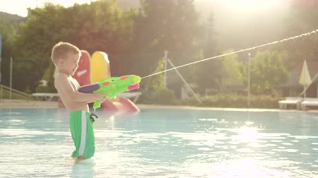 squirting : SLOW MOTION: Happy young boy kid having a fight with water gun at beautiful summer sunset in aquapark