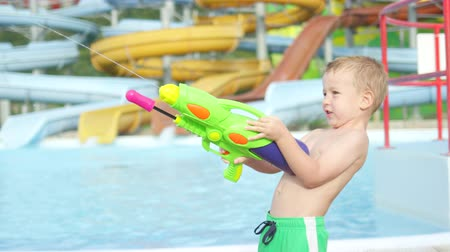 squirting : SLOW MOTION CLOSE UP: Happy kid shooting and squirting water with water gun in aqua park