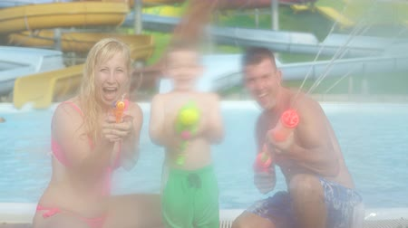 into the camera : SLOW MOTION: Smiling young family having a fun water fight, happy mother, father and their son shooting and squirting water with water guns directly into camera Stock Footage