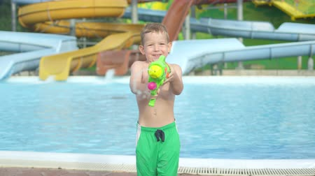 squirting : SLOW MOTION CLOSE UP: Happy smiling kid aiming and splashing water with water gun into camera in sunny summer