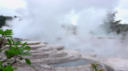 Big white steam smoke coming out of hot mineral water in beautiful geothermal terrace spring