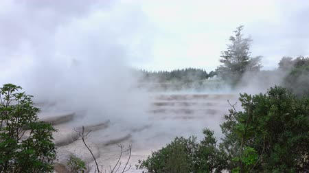 CLOSE UP: White smoke and steam rising from geothermal hot water terrace springs