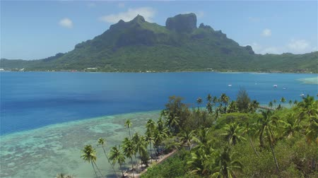 pacific islands : AERIAL: Flying above beautiful Bora Bora island resort with famous mountain on the main island and dreamy blue lagoon in sunny summer
