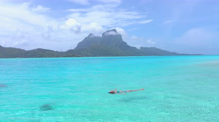 bora bora : Happy young woman swimming in perfect crystal clear Bora Bora lagoon on her summer vacation