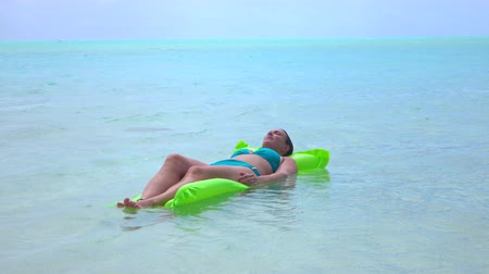 jangada : CLOSE UP: Relaxed young woman lying on inflatable water bed on exotic island Bora Bora Vídeos
