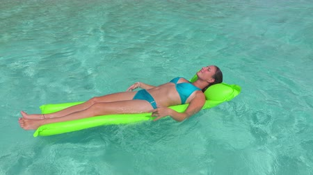 suntan : SLOW MOTION: Cheerful young woman laying and relaxing on inflatable air bed mattress floating on crystal clear ocean water surface on sunny summer vacation