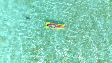 suntan : AERIAL: Happy young woman in swimsuit relaxing on airbed raft floating on emerald ocean on her summer vacation on sunny Bora Bora island resort