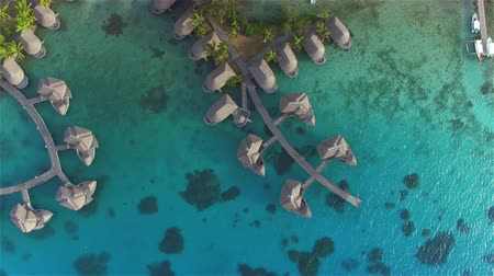 bora bora : AERIAL: Flying above luxury expensive overwater bungalow villas with spacious private rooms at high class hotel resort, facing gorgeous turquoise blue waters of fantastic Bora Bora lagoon on sunny tropical island