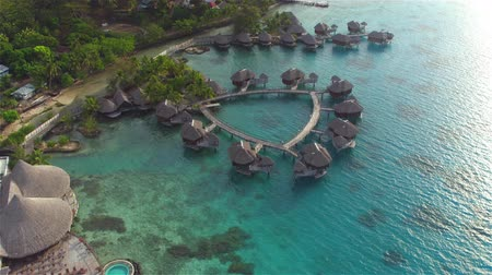 nyaraló : AERIAL: Flying above big luxury waterfront hotel on beautiful white sandy beach with deluxe overwater bungalows, fancy restaurants and outdoors swimming pool overlooking the perfect turquoise blue lagoon