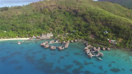 bungaló : AERIAL: Flying around deluxe hotel resort on beautiful secluded white sandy beach on exotic island Bora Bora in stunning French Polynesia