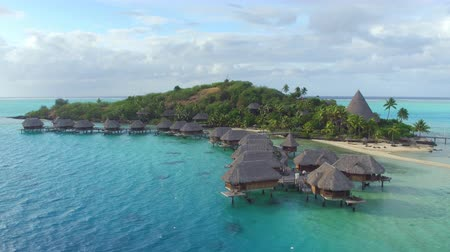 exclusivo : AERIAL: Luxurious private island resort with deluxe overwater bungalows and exclusive beachfront villas on small secluded motu island in Pacific ocean
