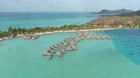 bungaló : AERIAL: Luxury hotel resort with deluxe overwater bungalows and secluded beachfront villas on beautiful tropical island with exotic white sand beach and turquoise blue lagoon reef