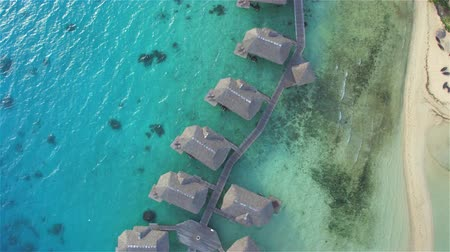 AERIAL: Luxury overwater bungalows and beachfront villas facing sparkling turquoise-blue waters of premium exotic beach on beautiful tropical island in the middle of blue lagoon in exquisite Bora Bora, offering a perfect honeymoon vacation Wideo