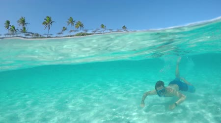 bora bora : SLOW MOTION UNDERWATER CLOSE UP: Happy young diver man on summer vacations snorkeling in crystal clear lagoon ocean in front of tropical island with exotic sandy beaches ant lush palm trees Stock Footage