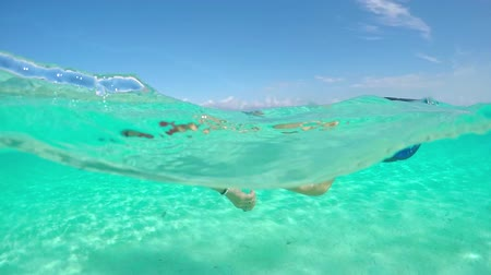 bora bora : SLOW MOTION HALF UNDERWATER CLOSE UP: Cheerful young woman swimming in sea and snorkeling in idyllic tropical island lagoon in French Polynesia on her fun summer vacation in paradise