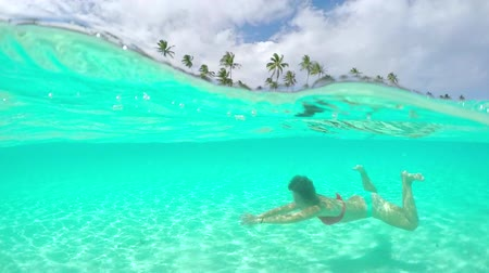 bora bora : SLOW MOTION UNDERWATER CLOSE UP: Happy young woman relaxing and swimming in perfect blue lagoon in front of tropical island with exotic white sandy beaches and palm trees on her summer vacations