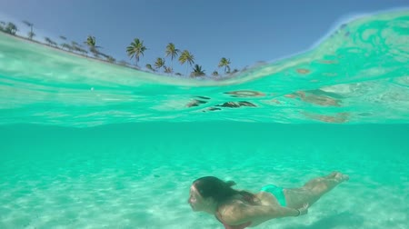 polinesia francesa : SLOW MOTION HALF UNDERWATER CLOSE UP: Happy young woman swimming under sea surface in fantastic shallow lagoon on her fun summer vacation on beautiful tropical island Archivo de Video