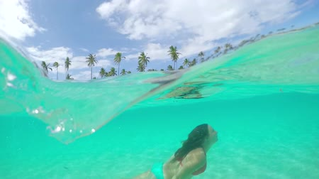bora bora : SLOW MOTION UNDERWATER CLOSE UP: Young female in bikini diving and swimming under the sea on fantastic tropical island with white sandy beaches and lush palm trees swaying in the summer wind Stock Footage