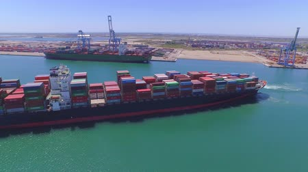 container terminal : AERIAL: Flying around freight container ship arriving to port