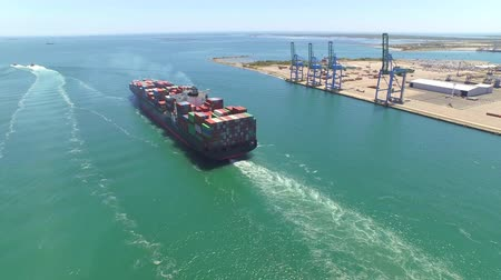 kontenery : AERIAL: Container ship, loaded with shipping freight containers leaving port, freight transportation Wideo