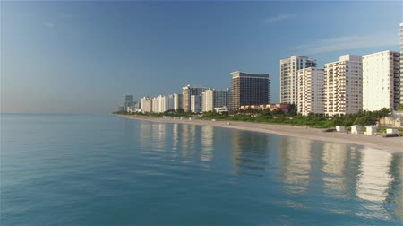 drone miami : AERIAL: Flying low above the ocean towards exotic sandy Miami Beach with tall skyscrapers in business district and beachfront buildings resort and hotels at beautiful sunny morning on summer day Stock Footage