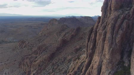 new mexico : AERIAL: Flying past rocky mountain wall in vast desert Stock Footage